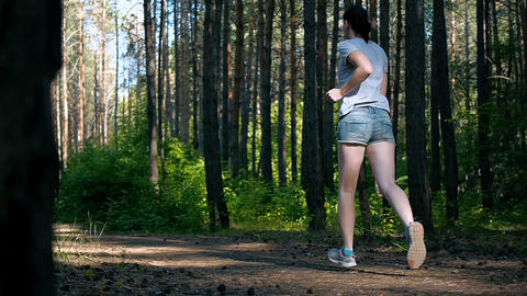 the girl ran down the path in the woods, outdoor fitness Archivo