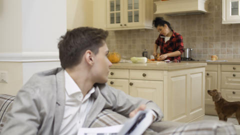 Young guy looks through documents and turns to girlfriend at the kitchen Footage