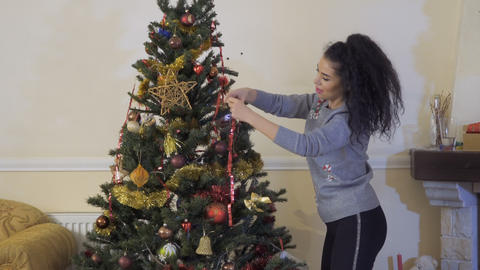 Young brunette decorated christmas tree with garland Live Action