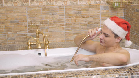 Handsome guy in santa hat takes a hot bath Footage