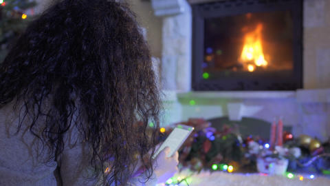 Young woman uses phone laying on floor near fireplace Footage