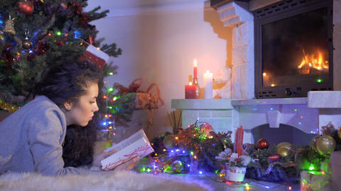 Pretty brunette read book laying near Christmas tree and fireplace Footage