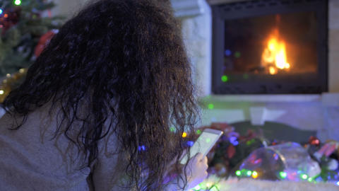 Woman lays near fireplace and send a festive messages to her friends Footage