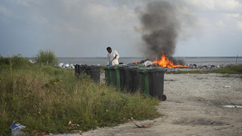 Controlled trash fire belching black smoke at landfill on Maafushi Island Footage