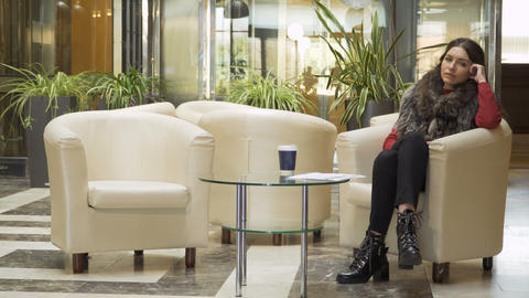 Young businesswoman waits in the lobby of hotel when the manager come to her Footage