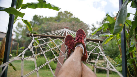 Close up of legs in sneakers of a man resting in a hammock on a sunny day Bild