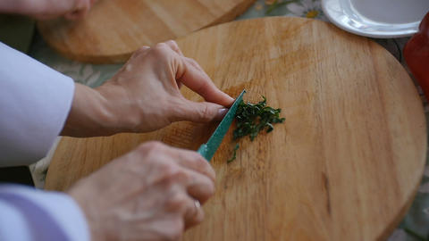 Woman hands preparing meal at the kitchen table. Prepare and chop lush greenery Live Action