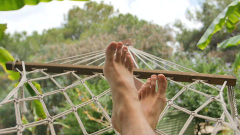 Close up of bare feet of a man resting in a hammock on a sunny day Live影片