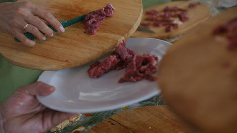 Putting multiple raw meat pieces into the dish Live Action