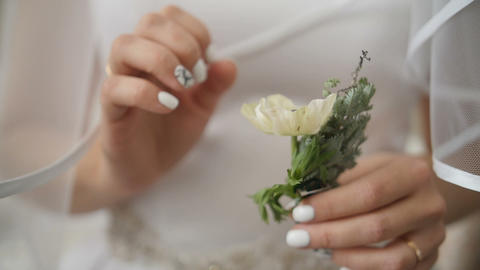 Bride holds boutonniere in her hands. Wedding preparation Footage