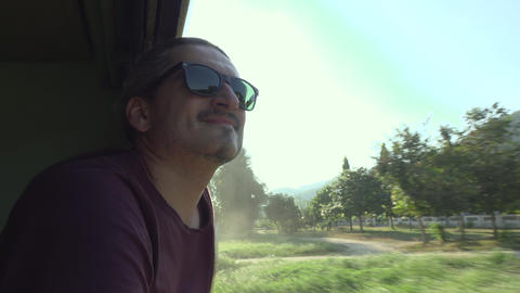 Smiling man Traveling On The Train Looking Out the open Window Footage