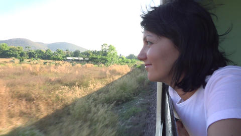 Slow motion video of a woman Traveling On The Train Looking Out the open Window Footage