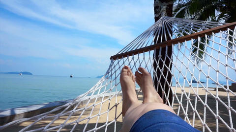 POV of Feet swinging in a hammock on coconut tree. Relaxing on the beach of Thai 影片素材