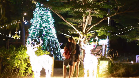 couple checking out christmas lights at thailand beach bar Footage