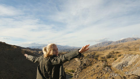 Young woman standing on the edge of the cliff and raising her hands up against Footage