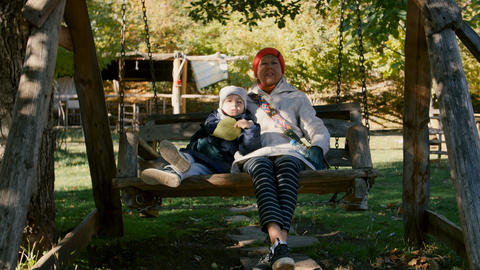 Grandmother and child ride on the wooden swing in the park outdoor in the Footage