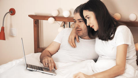 Happy couple choosing goods online and shopping using their laptop in bed Footage