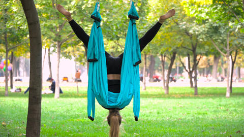 Girl in a park engaged in aerial yoga Fotografía