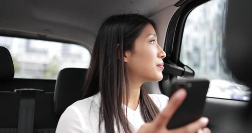 Businesswoman in taxi cab using smartphone Footage