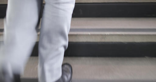 Close-up businessman's feet walking up staircase Footage