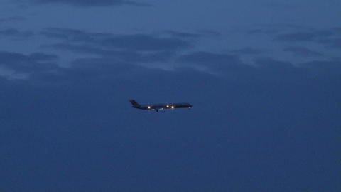 Plane flying across blue evening sky close up Footage