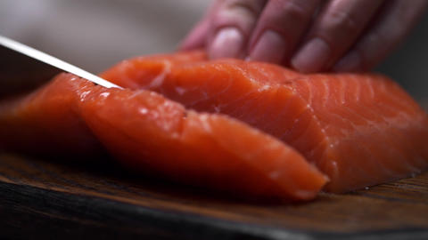 The cook cuts salmon fillet, chef slices fish for cooking, dishes with fish Live Action