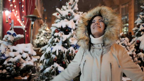 young woman enjoying winter evening and snowfall Photo