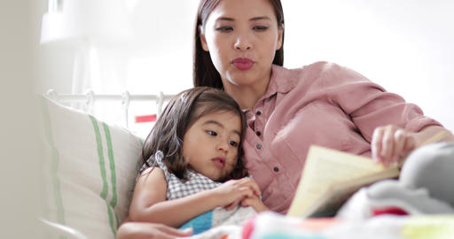 Mother reading Daughter a bedtime story Live Action