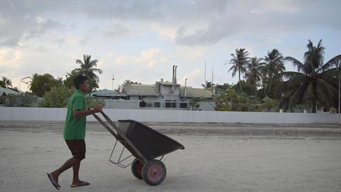 Local man pushes wheelbarrow along road near Maafushi diesel power station Live Action
