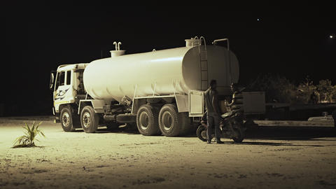 Man selling gasoline from a tanker truck on Maafushi Island at night Footage