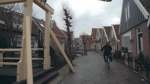 Unknown female cyclist riding along the street in a small Dutch town Footage