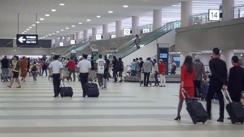 Travellers walking past baggage carousels at Don Muang International Airport Footage