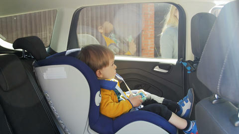 4k video of adorable baby boy sitting in child car safety seat Footage