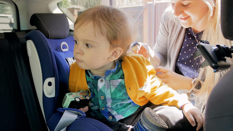 4k footage of young mother fastening seat belts on her childs car seat Live Action