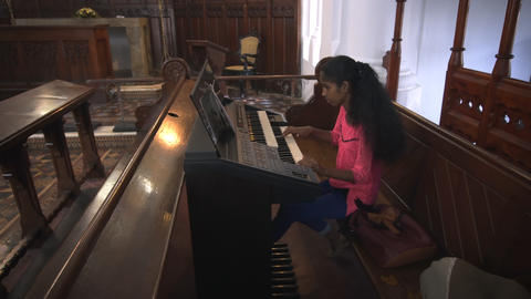 Girl practices on electronic keyboard inside Dutch Reformed Church in Galle Footage