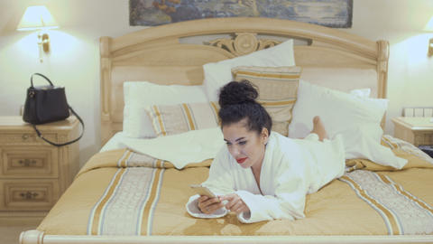 Attractive brunette in bathrobe lays on bed in hotel room and talks on phone Footage