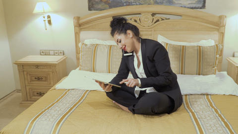 Businesswoman with red lips talks on phone and uses tablet in a hotel room Footage