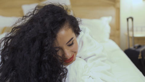 Beautiful curly brunette with red lips flirts with camera on the bed Footage