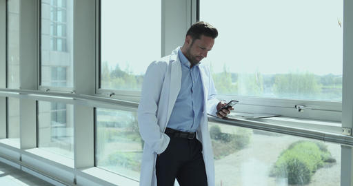Male medical professional using smartphone in corridor Footage