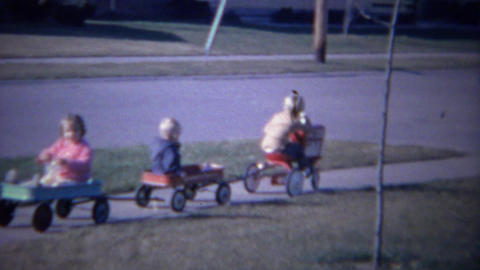 1961: Kid red tractor toy pulling cute wagon train on sidewalk Footage