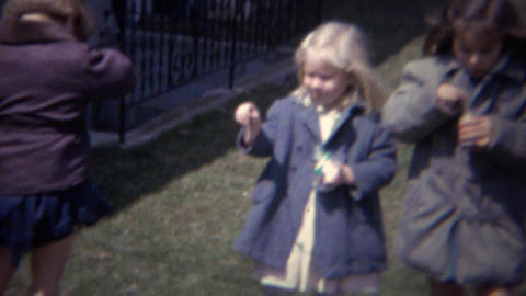 1961: Girls blowing bubbles in backyard gray formal dress coats Footage