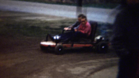 1961: Boys driving polluting go-kart in muddy circle homemade track Footage