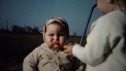 1962: Kid sister gives chubby baby faced brother hugs kiss on cheek Footage