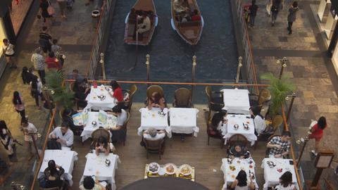 Boats passing beneath restaurant dining area at Shoppes at Marina Bay Sands Footage