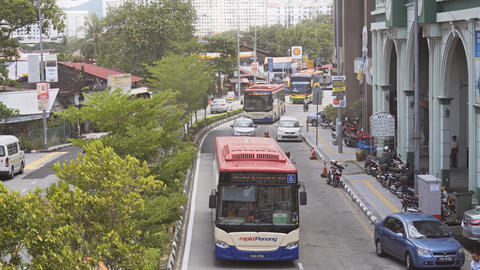 Buses and other traffic along a busy street in George Town Footage