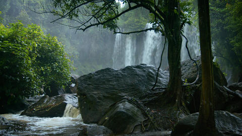 Rainy season in the tropics. Waterfall and a river among rocks and trees Footage