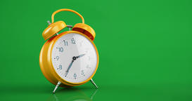 Yellow vintage alarm clock time lapse copy space green background Animación