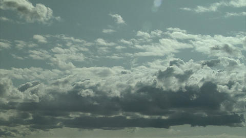 Puffy white clouds moving across blue sky on a sunny day Footage