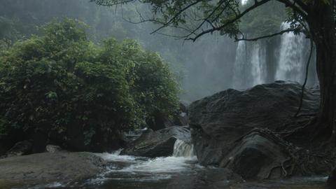 Rainy season in tropics. Waterfall and river among rocks. RAW 4k video Footage