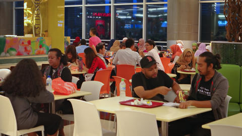Visitors enjoying a meal in a food court at Suria KLCC Mall Footage
